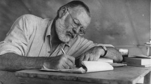 600px-Ernest_Hemingway_Writing_at_Campsite_in_Kenya_-_NARA_-_192655
