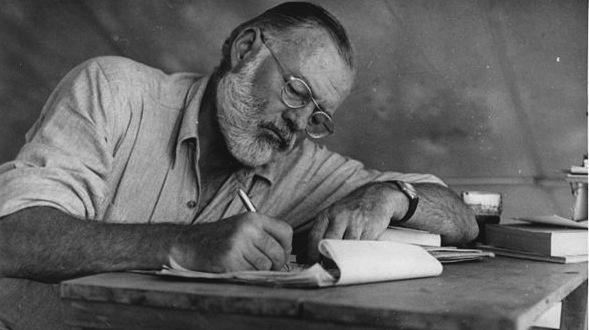 600px-Ernest_Hemingway_Writing_at_Campsite_in_Kenya_-_NARA_-_192655